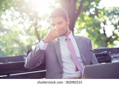 Businessman sitting at the bench in park and drinking coffee. Looking at camera