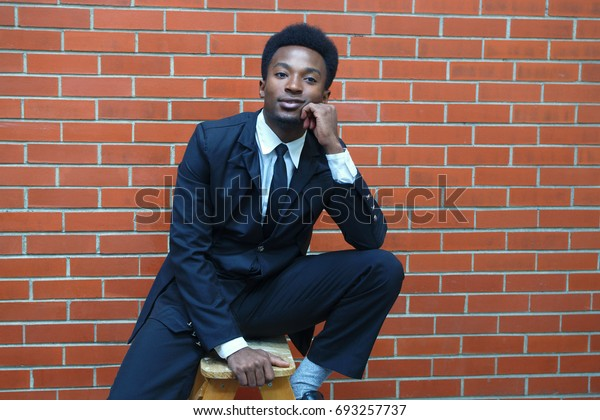 businessman sitting brick wall manager clothing professional smiling success young man
