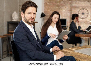Businessman sitting in busy office, looking at camera.