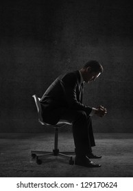 businessman sitting in a chair in concrete room