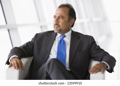 Businessman sitting in chair in office lobby