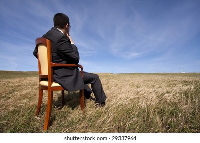 businessman sitting in a chair in outdoor looking to the field