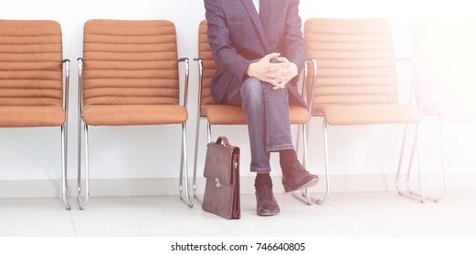 businessman sitting in a chair with a portfolio in anticipation