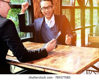 Businessman with sitting chair and raised their hands while using laptop in cafe, man using laptop and sitting with raised arms while feeling happy, concept of success working
