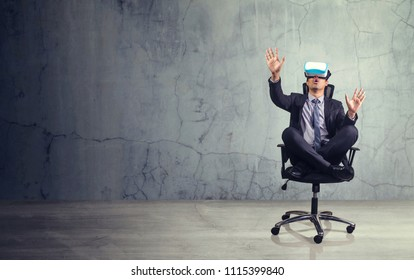 Businessman sitting in chair  wearing virtual reality glasses. Empty space for text or draw