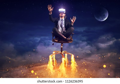 Businessman sitting in chair  wearing virtual reality glasses. Mixed media