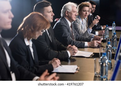 Businessman sitting at conference desk with colleagues