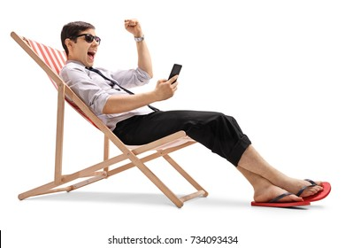 Businessman sitting in a deck chair looking at a phone and gesturing happiness isolated on white background