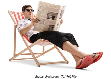 Businessman sitting in a deck chair and reading a newspaper isolated on white background