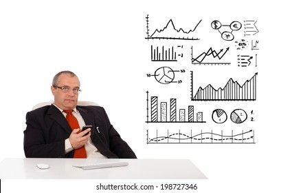 Businessman sitting at desk with diagrams and holding a mobilephone, isolated on white