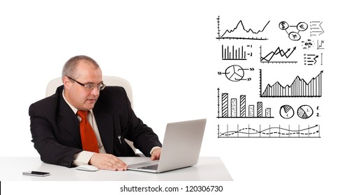 Businessman sitting at desk with diagrams and laptop, isolated on white