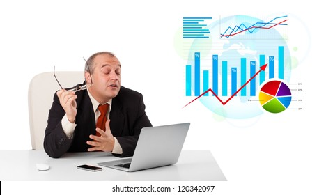 Businessman sitting at desk with laptop and statistics, isolated on white