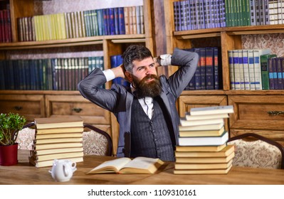 Businessman sitting at desk in office being busy studying books