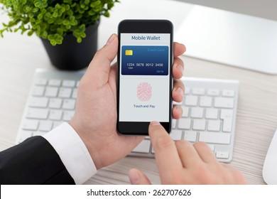бизнесмен сидит за столом в офисе и держит телефон с приложением мобильный кошелек и отпечаток пальца для интернет-покупок