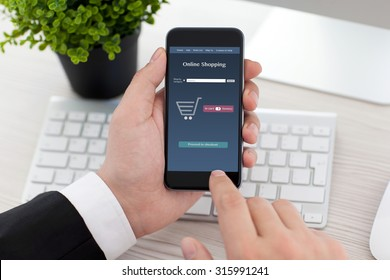 businessman sitting at the desk in office and holding phone with app online shopping on the screen