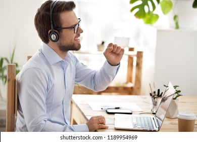 Businessman sitting at the desk in office room take a breath using pc have fun listening favourite music, song with headphones, positive emotions. Successful easy learning a foreign languages concept