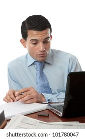A businessman sitting at desk with paperwork, laptop and notebook working hard.