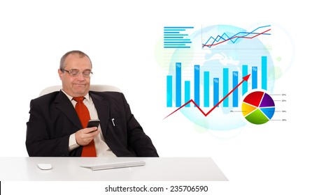 Businessman sitting at desk with statistics and holding a mobilephone, isolated on white