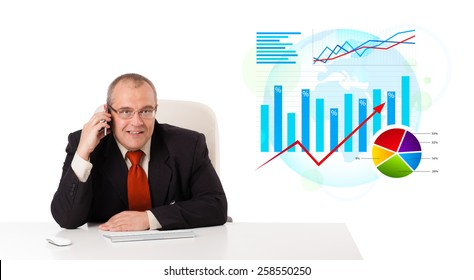 Businessman sitting at desk with statistics and making a phone call, isolated on white
