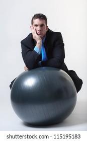 businessman sitting down on a gym fitness ball