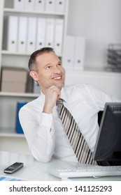 Businessman sitting in front of computer while looking at something