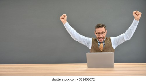 Businessman sitting in front of laptop with successful expression