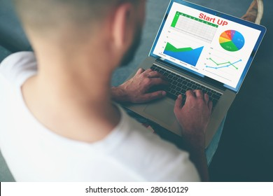 Businessman sitting front open laptop computer with financial information as graphics and charts,young entrepreneur working with statistics data on notebook indoors modern office,analyzing performance