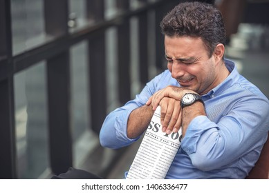 Businessman sitting, hand holding a newspaper and crying act. Businessman has a serious issue face.