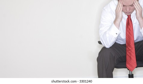 Businessman sitting in his chair with his hands on his hands in frustration and stress
