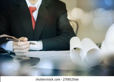 Businessman sitting at his desk reading documents