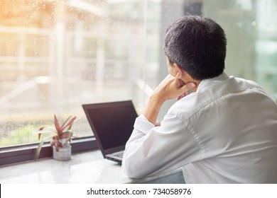 Businessman sitting with his lap top, watching the rain at outside.