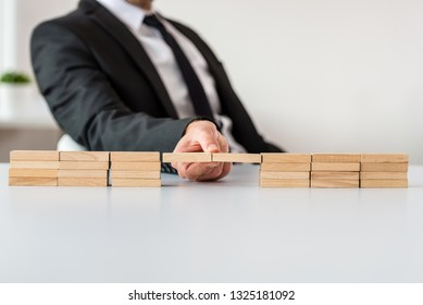 Businessman sitting at his office desk making a bridge of wooden pegs in a conceptual image of business merger.