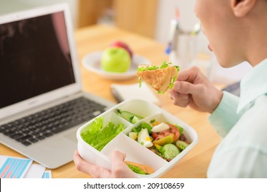 Businessman sitting at his table and eating salad for lunch