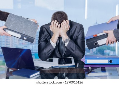 A businessman is sitting at his working place in the office closing his face with hands in working stress assault at the window big city panorama background. The concept of burnout syndrome.