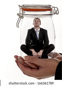A businessman sitting inside a glass jar as business concept for feeling trapped in the workplace. Feeling trapped.