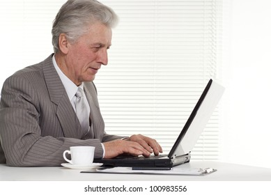 Businessman sitting at the laptop on a background