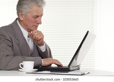 Businessman sitting at the laptop on a white background