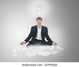 Businessman sitting in lotus position on a cloud with a light bulb over your head