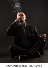 Businessman sitting in lotus position smokes a cigar and holding a glass of whiskey in his hand