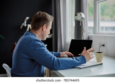 Businessman sitting in modern office and using laptop for work