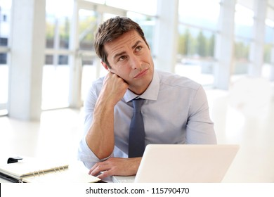 Businessman sitting in office with bored look