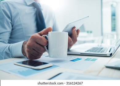 Businessman sitting at office desk having a coffee break, he is holding a mug and a digital tablet