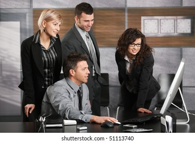 Businessman sitting at office desk, looking at screen together with colleagues, smiling.