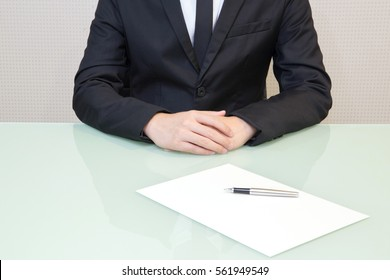 Businessman sitting at office desk waiting for someone sign a contract on white paper.for business blank screen and copy space about resume.