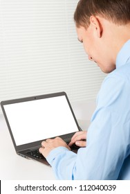 businessman sitting at office desk and working on laptop with blank screen