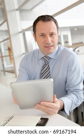 Businessman sitting in the office with electronic tab