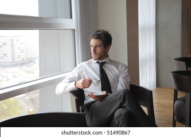 Businessman sitting in an office lounge with a cup of coffee