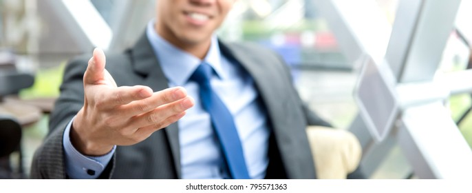 Businessman sitting in office lounge reaching out hand with open palm, welcome gesture - panoramic banner