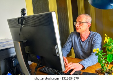Businessman sitting in an office at the . Middle aged man with glasses sitting at desk. Mature man using mobile phone. Senior concept.
