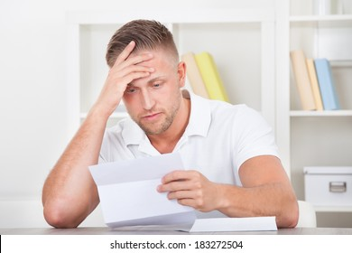 Businessman sitting in an office reacting in shock to the contents of a letter that he is reading raising his hand to his mouth